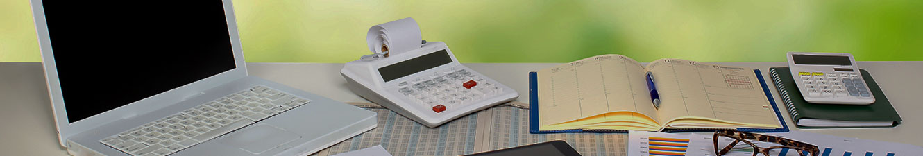 Laptop, calculators, glasses, chart and ledger on a table