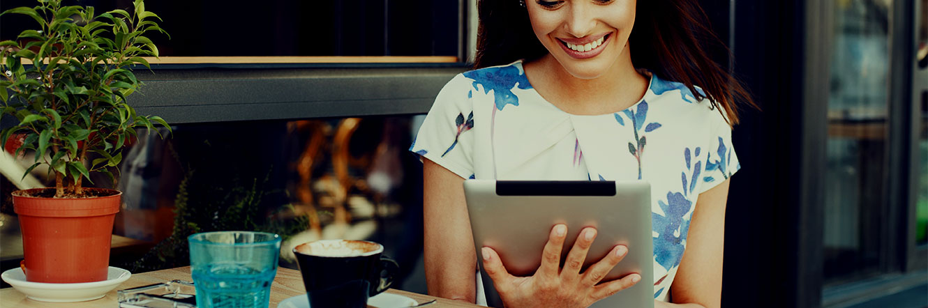 Woman on an tablet smiling while she sits outside drinking coffee