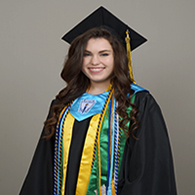 female high school graduate in cap and gown with several graduation cords